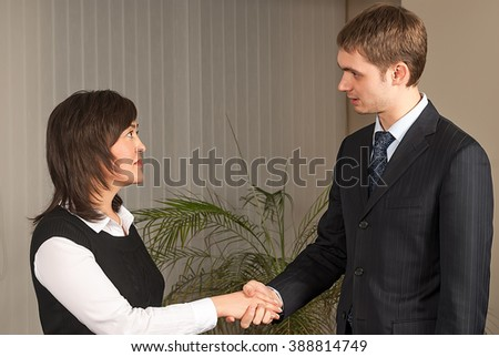 Business handshake - two businesspeople shaking hands to conclude deal or agreement - stock photo