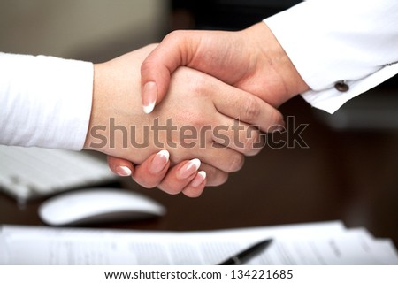 Business handshake: two businesswomen handshaking over table with  agreement - stock photo