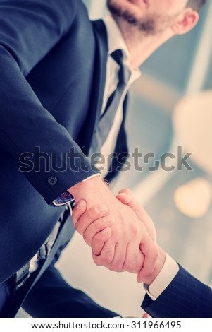 Business handshake. Two successful businessman standing in the restaurant and drink coffee while shaking hands with each other close-up view of hands