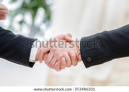 Business handshake. Two successful businessman standing in the restaurant and drink coffee while shaking hands with each other close-up view of hands - stock photo