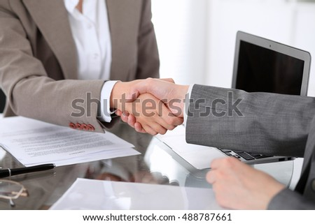 Business handshake. Two women lawyers are shaking hands after meeting or  negotiation.