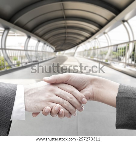 Business handshake with blur tunnel bridge building background,growing together in business concept. - stock photo