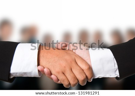 Business handshake with business people background - stock photo