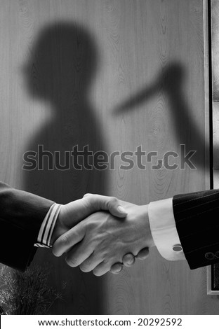 business handshake with shadows behind showing  real intentions showing a man being stabbed in the back - stock photo