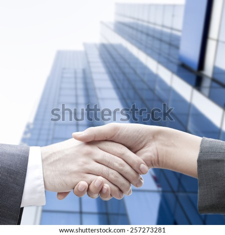 Business handshake with the modern blur building background - stock photo