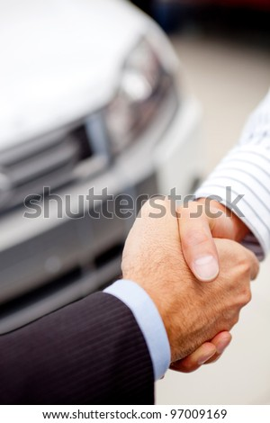 Business handshaking to close the deal after buying a car - stock photo