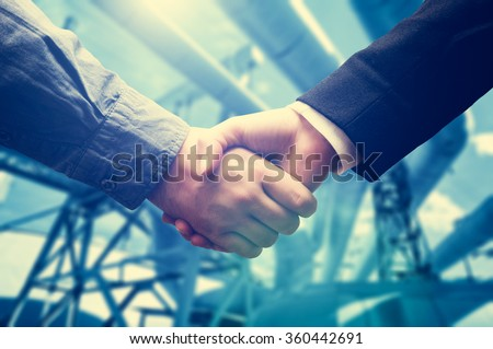 Business handske next to thermal electic power station, factory. Deal in the industry - stock photo