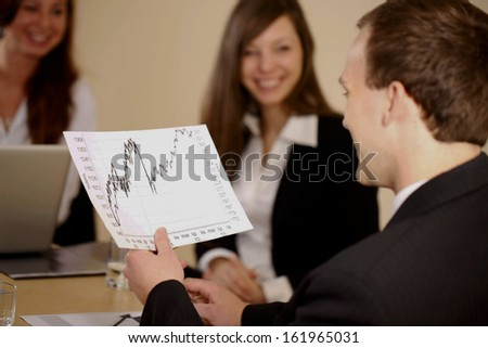 Business holding a chart and working with young girls in the office - stock photo