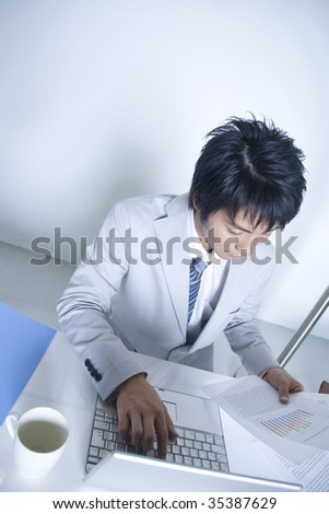 BUSINESS IMAGE-a businessman using a laptop PC and checking the documents
