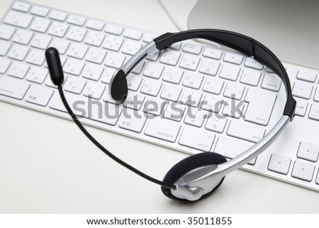BUSINESS IMAGE-a headset on a white keyboard - stock photo