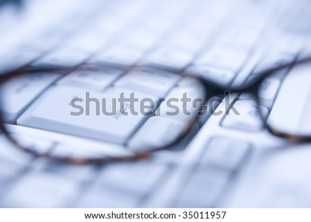 BUSINESS IMAGE-close-up shot of a pair of glasses on the white keyboard