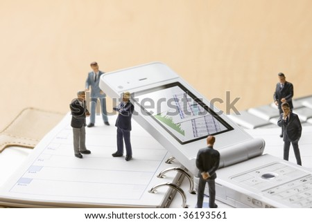 BUSINESS IMAGE-six models of people holding a meeting around the white mobile phone - stock photo