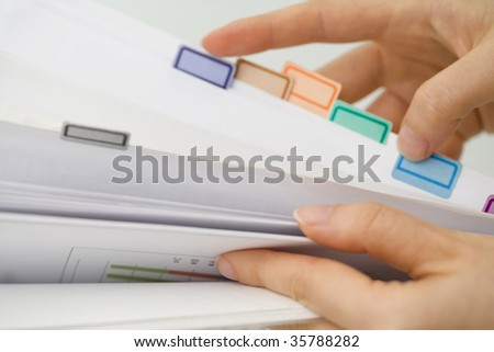 BUSINESS IMAGE-woman's hands turning over the sheet of file - stock photo