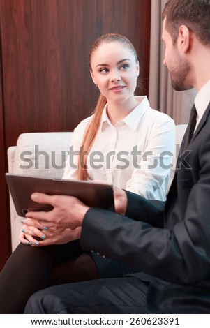 Business in digital age. Two cheerful business people in formalwear discussing something and smiling while one of them sitting from behind pointing digital tablet