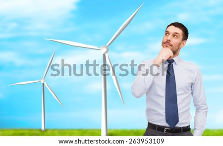 business, innovation, energy saving and people concept - handsome businessman looking up over windmills and blue sky background