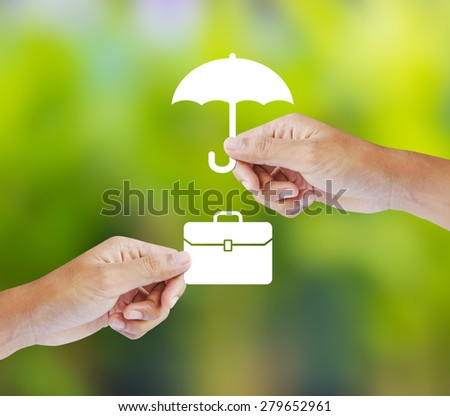 Business insurance concept with an umbrella covering business briefcase