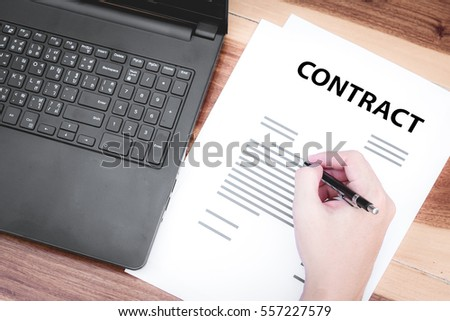 business insurance lawyer concept : hand using pen sign business contracts agreement paper ,selective focus.