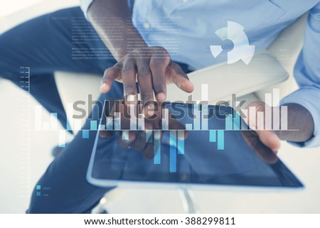 Business interface with graphs and data against businessman using digital tablet while sitting on chair - stock photo
