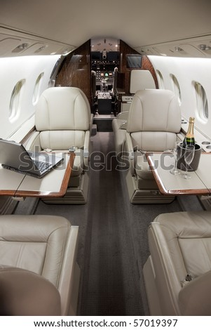 Business Interior Jet Airplane with computer laptop and Champagne on the tables. - stock photo