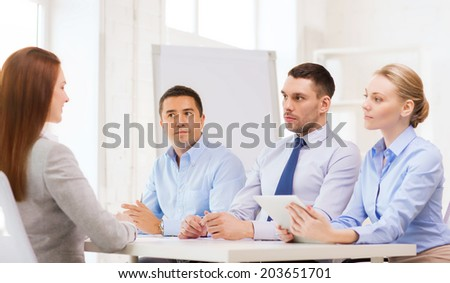 business, interview, employment and office concept - business team with tablet pc computer interviewing or firing worker in office - stock photo