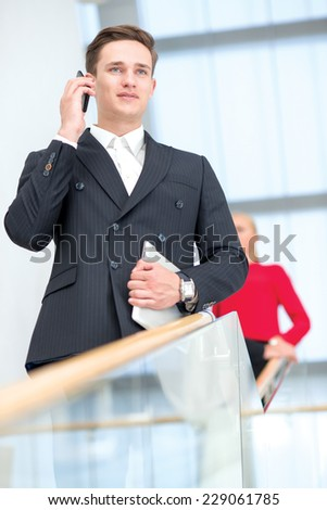 Business issue is solved by the mobile phone. Young successful and motivated businessman is standing with tablet and speaking on the mobile phone. - stock photo
