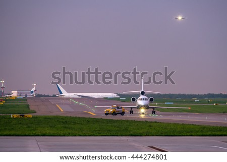 """Business jet taxiing on airport runway after """"follow me"""" car while passenger aircraft on final approach for landing and another passenger aircraft taxiing for take off - stock photo"""