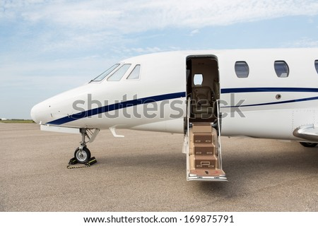 Business jet with open door parked at terminal - stock photo