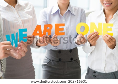 Business ladies holding letters as a symbol of the cooperation - stock photo