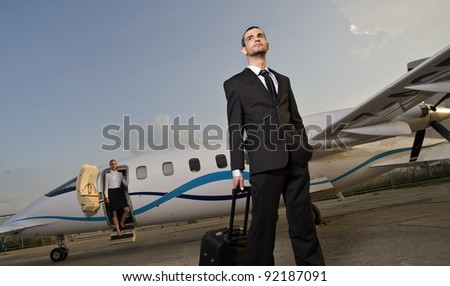 Business lady and businessman coming out of an airplane - stock photo