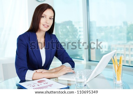 Business lady at workplace looking at camera - stock photo