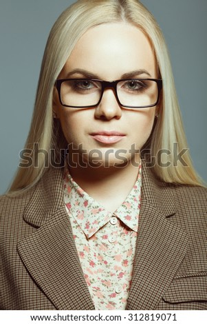 Business lady concept. Portrait of young beautiful blonde girl wearing trendy glasses, casual shirt, jacket and posing over gray background. Close up. Studio shot - stock photo
