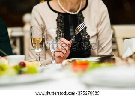 Business lady dines in a restaurant, hand with fork