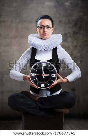 Business lady in ruff collar with a clock looking at camera - stock photo