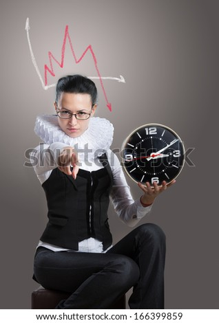 Business lady in ruff collar with a clock pointing at the camera - stock photo