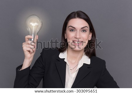 Business lady posing with bulb in her hand. Woman with long hair in black business suit happy smiling because of having new ideas.