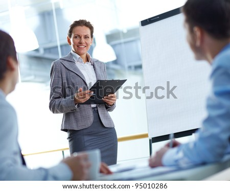 Business lady presenting a project to her colleagues - stock photo