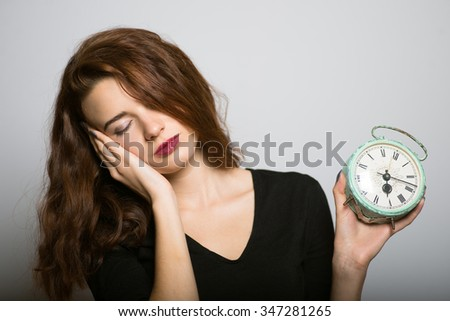 Business lady slender wants to sleep with the alarm clock, studio shot isolated on the gray background - stock photo