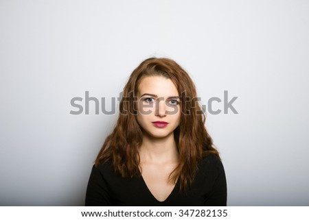 Business lady slim portrait with a serious face, studio shot isolated on the gray background