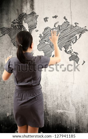 Business Lady touching world map drawing on the wall.