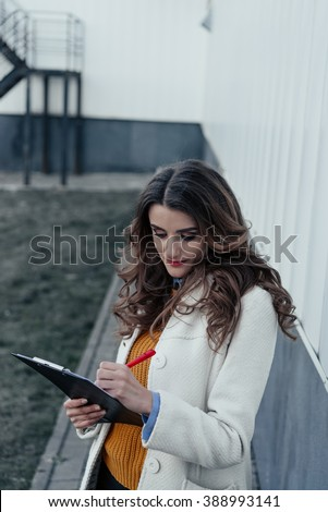 Business lady with a tablet and pen outdoors