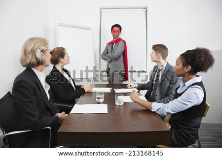 Business leader as superhero in front of colleagues at meeting in conference room - stock photo