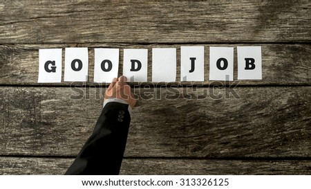 Business leader assembling phrase GOOD JOB with white cards with letters on them on wooden background in order to compliment and encourage his team of employees for further successful endeavours. - stock photo