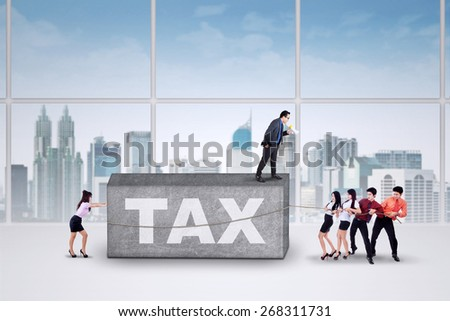 Business leader commanding his employee to pull a rock with a text of tax - stock photo