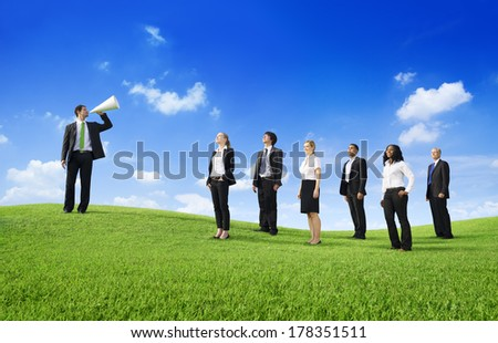 Business Leader Shouting at Team on a Green Hill - stock photo