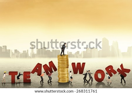 Business leader with his team arrange a teamwork text together, shot outdoors - stock photo