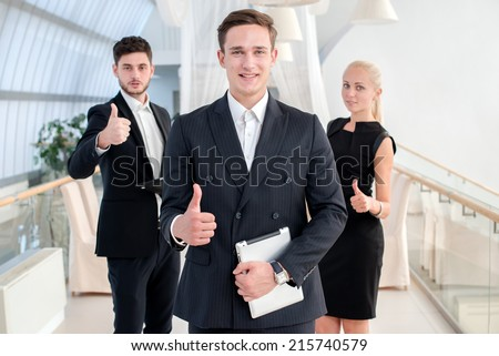 Business leader. Young man in formal wear holding a the tablet and smiling at the camera and showing thumbs up while standing and his colleagues showing a thumbs up on a background - stock photo