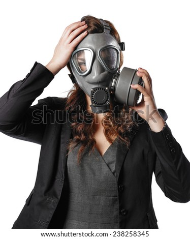 Business looking young adult woman put on a personal gas mask on her face - white background - stock photo
