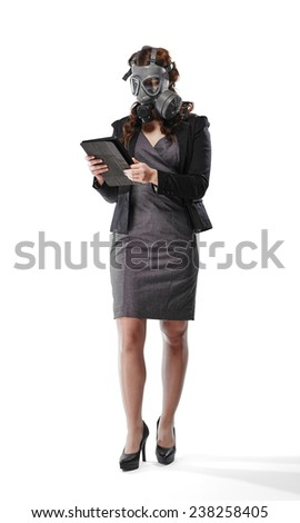 Business looking young adult woman wearing a personal gas mask and she use a tablet computer - white background - stock photo