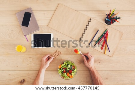 Business lunch at working place. Businessman in office. Hands of eating man. Healthy, diet food, vegetable salad with apple and juice. Notebook, tablet and pencils. Top view, flat lay - stock photo