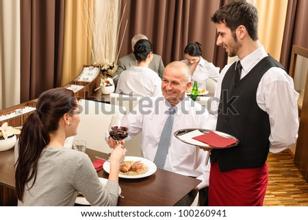 Business lunch executive people toast with red wine young waiter serve